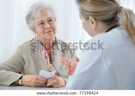 doctor explaining diagnosis to his female patient - stock photo