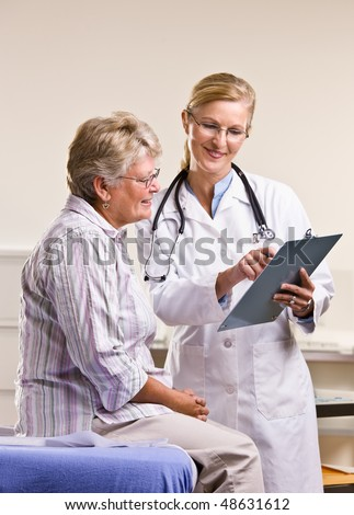 Doctor explaining medical chart to senior woman - stock photo