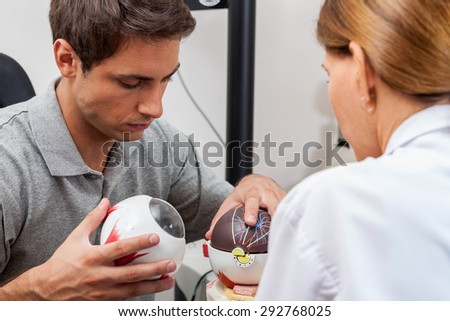 Doctor explaining to the patient about the eye - stock photo