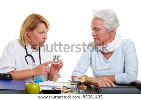 Doctor explaining usage of medication to senior woman - stock photo