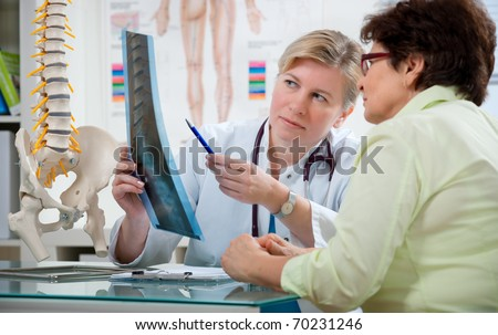 Doctor explaining x-ray results to patient - stock photo