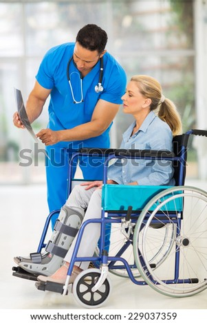 doctor explaining x-ray results to patient in wheelchair - stock photo