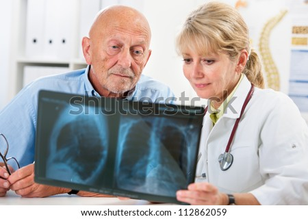 Doctor explaining x-ray results to senior patient - stock photo