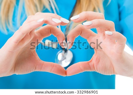 Doctor expressing abstractly her love towards her occupation - hearth shape, cardiology concept. - stock photo