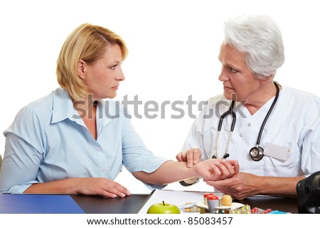 Doctor feeling pulse of female patient with her fingers - stock photo