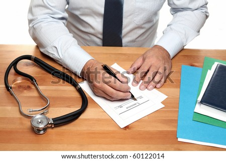 Doctor filling out Prescription. - stock photo