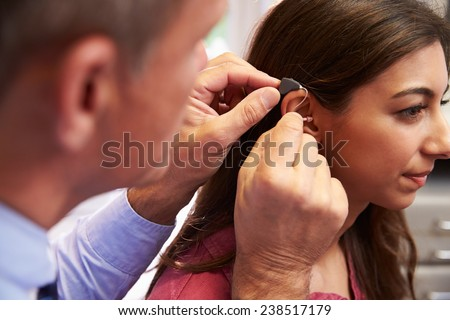 Doctor Fitting Female Patient With Hearing Aid - stock photo