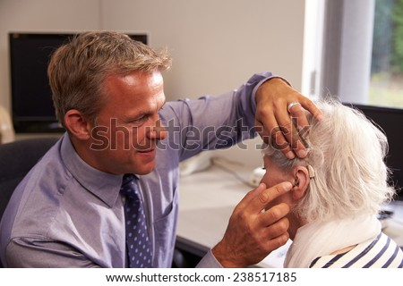 Doctor Fitting Senior Female Patient With Hearing Aid - stock photo