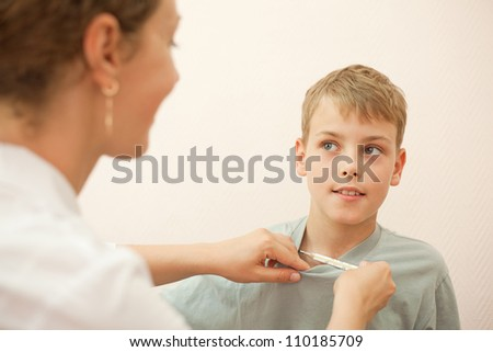 Doctor gives thermometer little boy and hold his t-shirt, focus on boy - stock photo