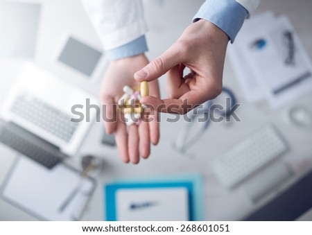 Doctor giving a lot of multicolor pills and tablets, hands close up with desktop on background, top view - stock photo
