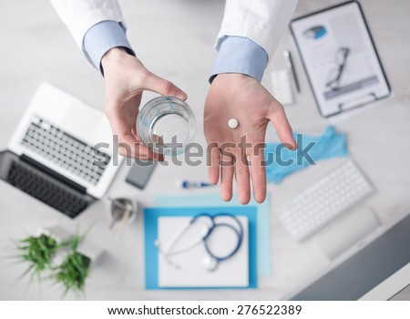 Doctor giving a pill and holding a glass of water, desktop with medical equipment and computer on background, hands close up top view - stock photo