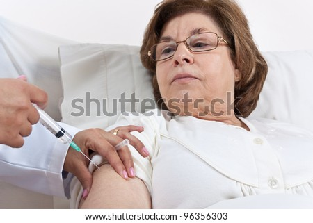 Doctor giving an injection onto a Senior Patient Arm - stock photo