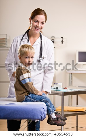 Doctor giving boy checkup in doctor office - stock photo