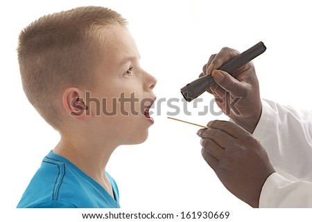 Doctor giving boy checkup - throat examination   - stock photo