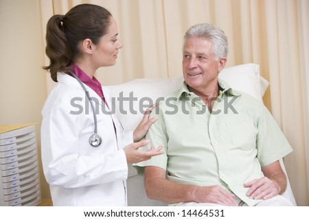 Doctor giving checkup to man in exam room smiling - stock photo