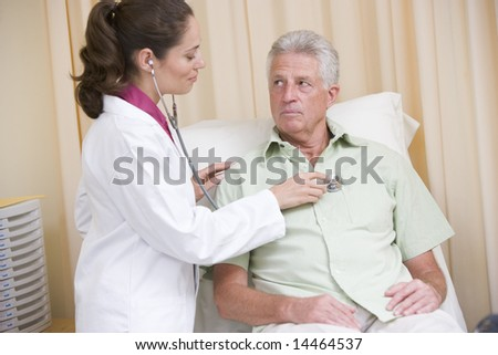 Doctor giving checkup with stethoscope to man in exam room - stock photo