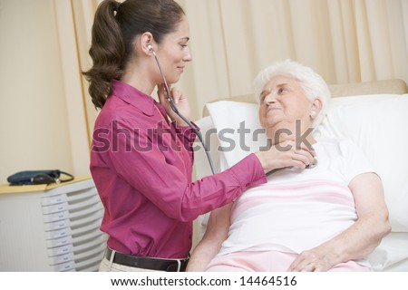Doctor giving checkup with stethoscope to woman in exam room smiling - stock photo