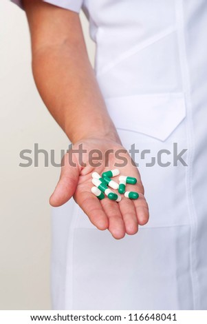 Doctor giving or showing pills or capsules on stretched hand close-up. Selective focus on the pills. The concept of medical care - stock photo