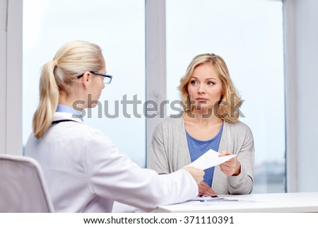 doctor giving prescription to woman at hospital