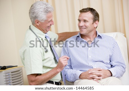 Doctor giving smiling man checkup in exam room - stock photo