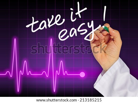 Doctor hand writing message TAKE IT EASY! with heart rate monitor in the background - stock photo
