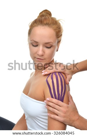 Doctor hands applying special physio tape on woman shoulder isolated on a white background - stock photo