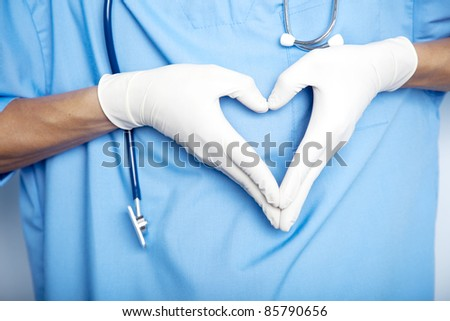 Doctor hands in gloves in the shape against the background of his body. closeup - stock photo