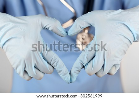 Doctor hands in gloves making shape of heart, closeup - stock photo