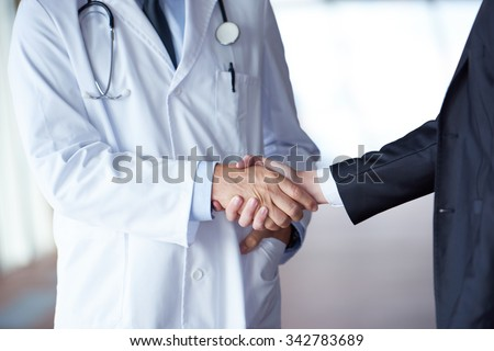 doctor handshake with a patient at doctors bright modern office in hospital - stock photo