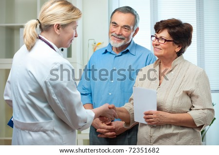 doctor handshaking with a senior couple - stock photo