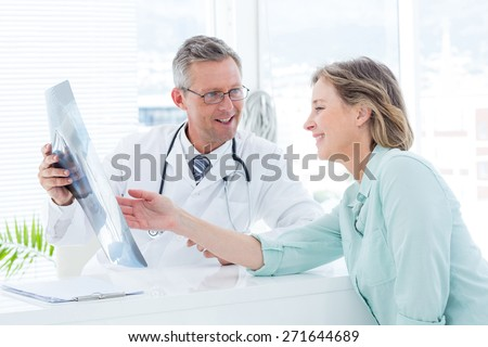Doctor having conversation with his patient and holding xray in medical office - stock photo
