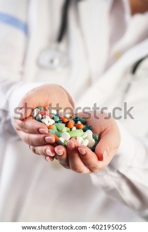 Doctor having her hands filled with pills. Overdose concept