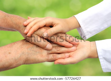 Doctor helping senior in nature - stock photo