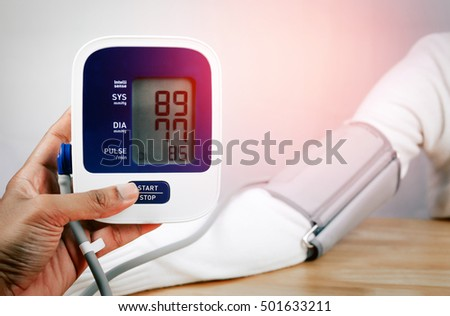 doctor holding a digital blood pressure monitor with patient
