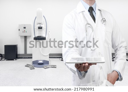 doctor holding a digital tablet at mammography breast screening modern device in hospital laboratory  - stock photo