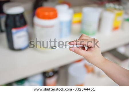 Doctor holding a medical thermometer in medical office