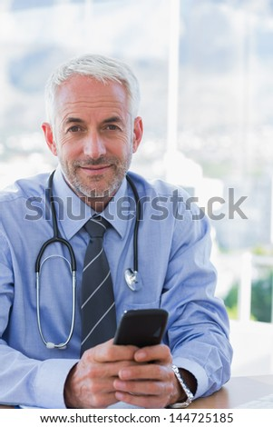 Doctor holding a mobile phone and looking at camera - stock photo