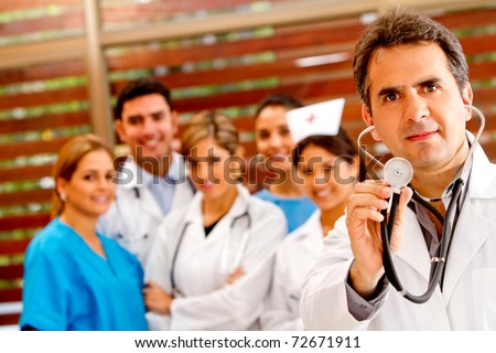 Doctor holding a stethoscope at the hospital with a  group behind - stock photo