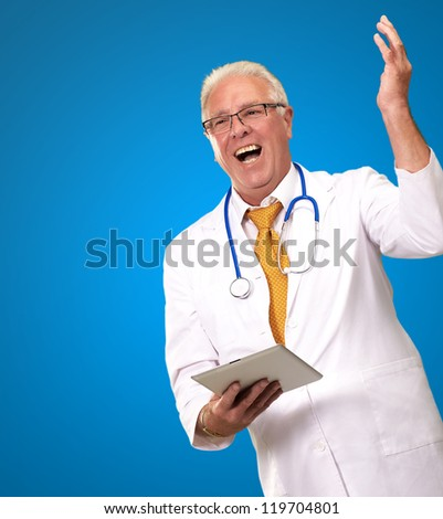 Doctor Holding A Tablet And Happy On Blue Background - stock photo