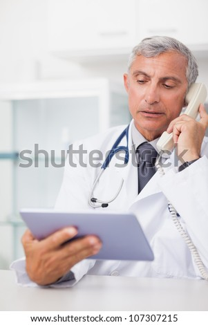 Doctor holding a tablet computer while calling in hospital ward - stock photo