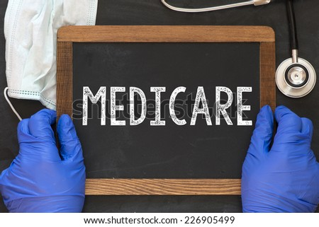 Doctor holding blackboard in hands with the word medicare - stock photo