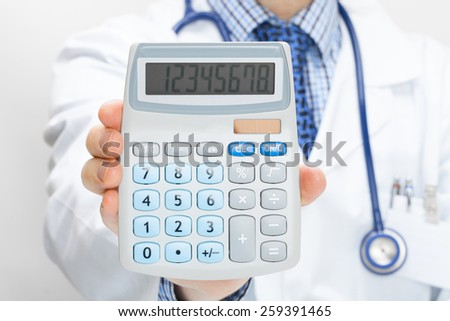 Doctor holding calculator in hand - health care concept - stock photo