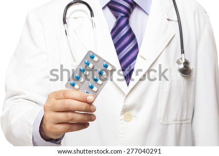 Doctor holding capsule on white background - stock photo