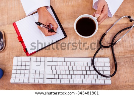 Doctor holding coffee cup and writing on diary on desk - stock photo