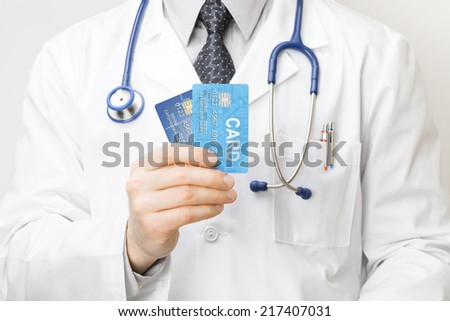 Doctor holding credit cards in his hand - closeup studio shot - stock photo