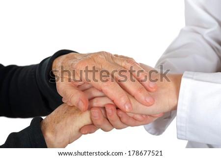 Doctor holding elderly hand on isolated background - stock photo