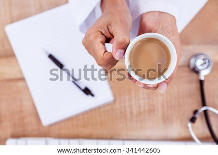 Doctor holding hot beverage on desk at work - stock photo
