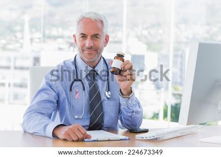 Doctor holding medicine jar wearing breast cancer awareness ribbon - stock photo