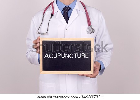 Doctor holding mini blackboard with ACUPUNCTURE message - stock photo