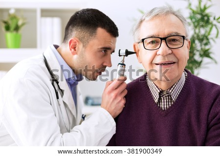 Doctor holding otoscope and examining senior patient ear - stock photo